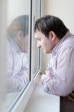 Mens die het venster bekijkt royalty-vrije stock afbeelding