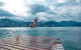 Mens die in het water van de pijler springen royalty-vrije stock fotografie