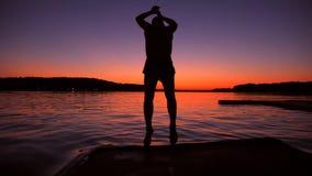 Mens die in het Water van Houten Pier During Amazing Sunset springen De super Langzame Levensstijl van de de Zomervrijheid van Mo stock footage