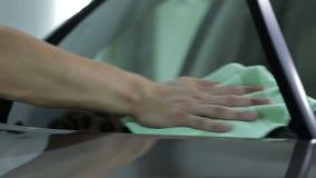 Mens die het windscherm van een auto afvegen stock footage