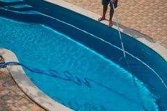 Mens die het zwembad met stofzuiger schoonmaken Royalty-vrije Stock Afbeeldingen