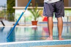 Mens die het zwembad schoonmaakt Stock Foto's