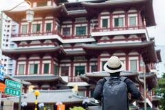 Mens die hipster met rugzak en hoed, solo reiziger reizen die aan de Tempel van het de Tandoverblijfsel van Boedha in Chinatown v royalty-vrije stock foto