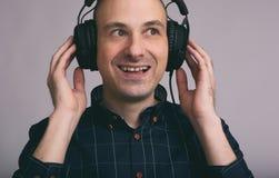 Mens die in hoofdtelefoons aan muziek luistert Stock Foto