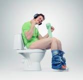 Mens die in hoofdtelefoons op het toilet zitten Ja! Stock Foto