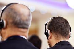 Mens die hoofdtelefoons voor vertaling met behulp van stock afbeeldingen