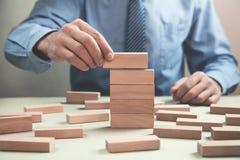Mens die houten blokken stapelen Het concept van de ontwikkeling royalty-vrije stock foto