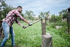 Mens die houten en scherp brandhout met bijl verdelen Stock Fotografie