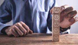 Mens die houten kubus tonen Classificatietevredenheid Terugkoppeling in vorm van emoties stock afbeelding
