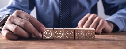 Mens die houten kubus tonen Classificatietevredenheid Terugkoppeling in vorm van emoties stock fotografie