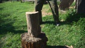 Mens die houten logboeken met bijl hakken stock videobeelden