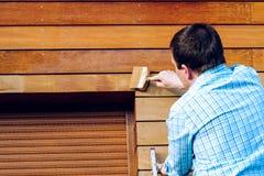 Mens die houten muur met een borstel schilderen stock foto's