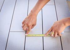 Mens die houtvloer met het meten van band meten Royalty-vrije Stock Foto