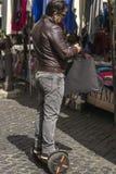 Mens die hoverboard bij markt op gebied van bloemen gebruiken royalty-vrije stock foto's