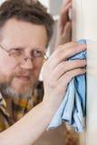 Mens die huishoudenkarweien doen Stock Foto's