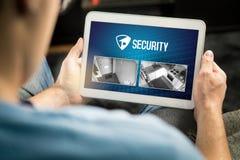 Mens die huisveiligheidssysteem en toepassing in tablet gebruiken royalty-vrije stock foto