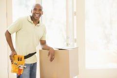 Mens die hulpmiddelriem draagt door dozen in nieuw huis Stock Afbeelding