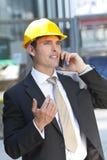 Mens die in Industriële Bouwvakker op de Telefoon van de Cel spreekt Stock Foto's