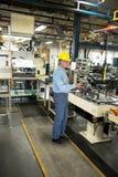 Mens die in Industriële Productiefabriek werken stock foto