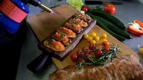 Mens die Italiaanse bruschetta met gebakken tomaten, basilicum en kaas voorbereiden Italiaanse voedsel langzame motie stock footage