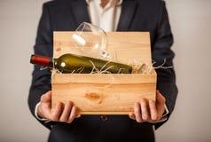 Mens die in jasje open doos met fles wijn houden Stock Afbeeldingen