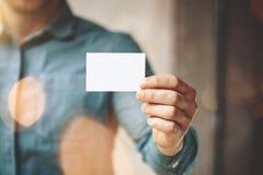 Mens die jeansoverhemd dragen en leeg wit adreskaartje tonen Vage achtergrond horizontaal Model Stock Foto
