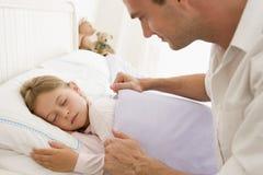 Mens die jong meisje in bed het glimlachen wekt Royalty-vrije Stock Foto