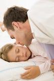 Mens die jong meisje in bed met kus wekt Stock Afbeeldingen