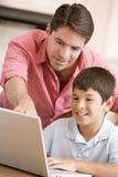 Mens die jonge jongen in keuken met laptop helpt Royalty-vrije Stock Fotografie