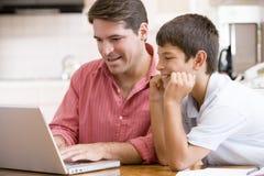 Mens die jonge jongen in keuken met laptop helpt stock foto's