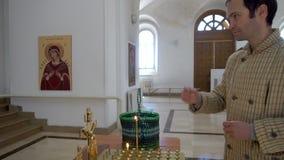 Mens die Kaars zetten en in Kerk, Permanent, Rusland kruisen - 25 Mei 2017 stock video