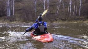 Mens die kayaker in een boot tegen de stroom roeien stock video