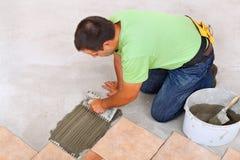 Mens die keramische tegelsvloer leggen die - de kleefstof uitspreiden stock foto