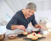 Mens die in keuken gebakjes voorbereiden royalty-vrije stock fotografie
