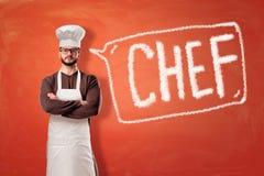 Mens die keukenschort en chef-kokhoed met een teken op rode achtergrond dragen royalty-vrije stock afbeeldingen