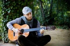 Mens die klassieke gitaar speelt Stock Fotografie