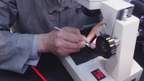 Mens die kleine inschrijving op medaillons graveren die microscoop gebruiken stock videobeelden
