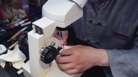 Mens die kleine inschrijving op medaillons graveren die microscoop gebruiken stock footage