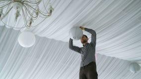Mens die kleurrijke witte roze grijze document lantaarns hangen aan plafond stock videobeelden