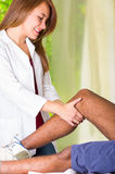 Mens die kniebehandeling van fysiotherapeut, haar handen krijgen die zijn been houden en massage, verwondings medisch concept toe Royalty-vrije Stock Fotografie