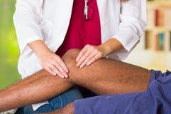 Mens die kniebehandeling van fysiotherapeut, haar handen krijgen die zijn been houden en massage, verwondings medisch concept toe Stock Afbeeldingen