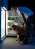 Mens die koelkast onderzoekt Royalty-vrije Stock Afbeelding