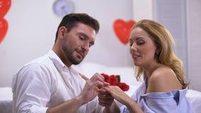 Mens die kostbare verlovingsring op gelukkige damevinger zetten, die voorstel doen stock footage