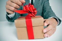 Mens die in kostuum een gift openen royalty-vrije stock fotografie