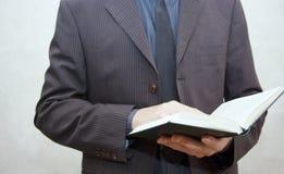 Mens die in kostuum een open boek houden Stock Afbeeldingen