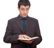 Mens die in kostuum een open boek houden Royalty-vrije Stock Foto's