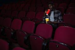 Mens die koude drank hebben terwijl het letten van op film stock fotografie