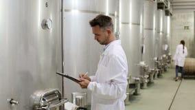 Mens die laag dragen die gegevens van materiaal in wijnmakerij opstijgen stock footage