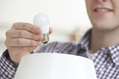 Mens die Lage Energie LEIDENE Lightbulb thuis zetten in Lamp Royalty-vrije Stock Foto's