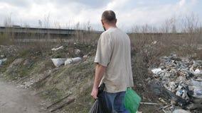 Mens die langs huisvuilstortplaats lopen met afvalbakken stock video